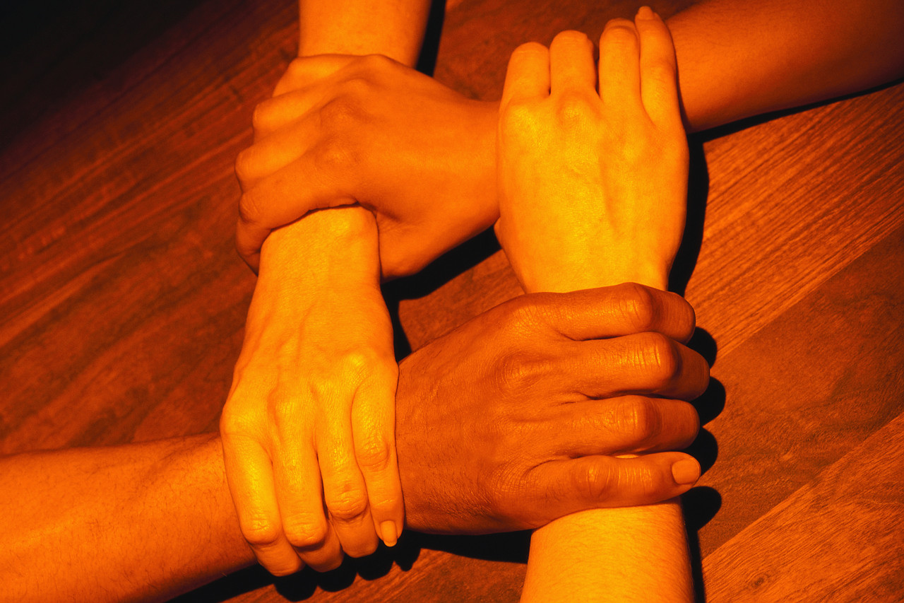 The crossed hands of teamwork.
